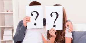 Couple on Couch With Question Marks In Front of Faces